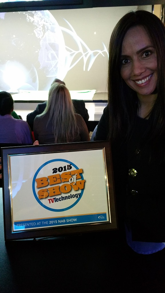 NewTek's Maria Torres beams as she holds the Best of Show Award for TalkShow from TV Technology.